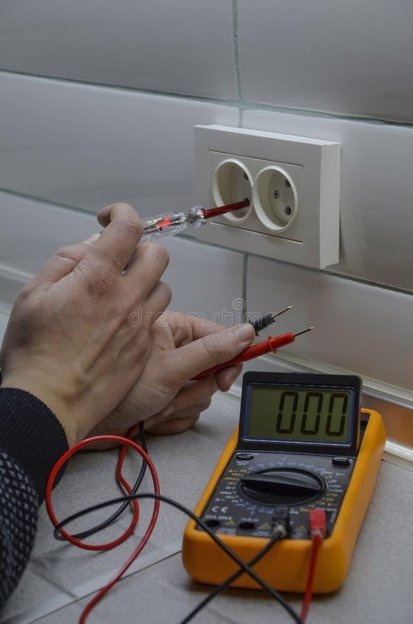 Medidas del electricista con el probador del multímetro fotografía de archivo