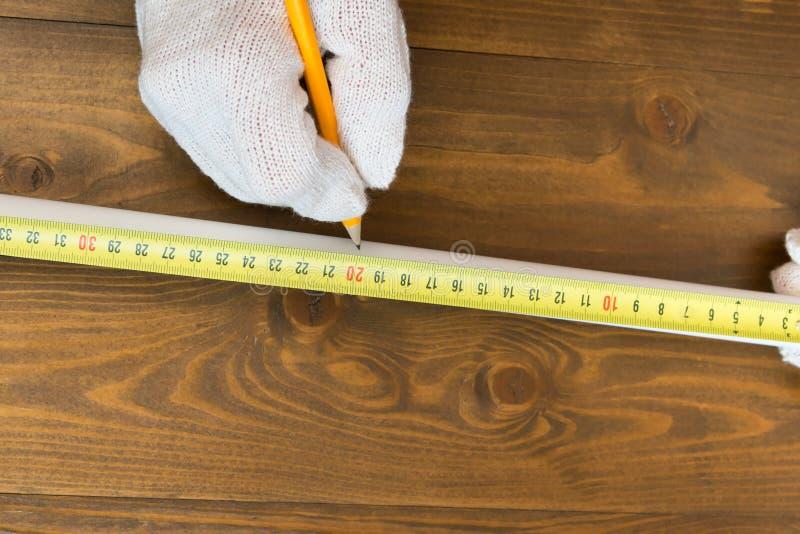 Medidas mestras um a parte da tubulação branca usando uma fita métrica em um fundo de madeira fotografia de stock royalty free