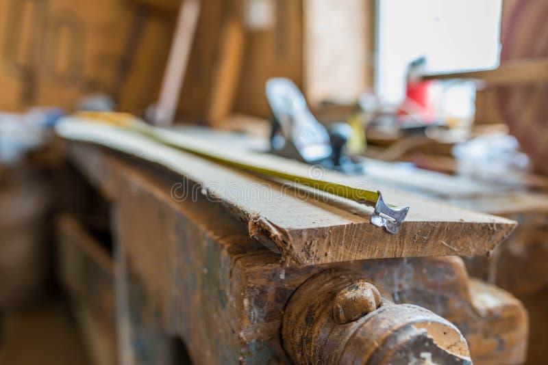 Medidor da fita na placa longa do carvalho em uma oficina de madeira pequena imagem de stock