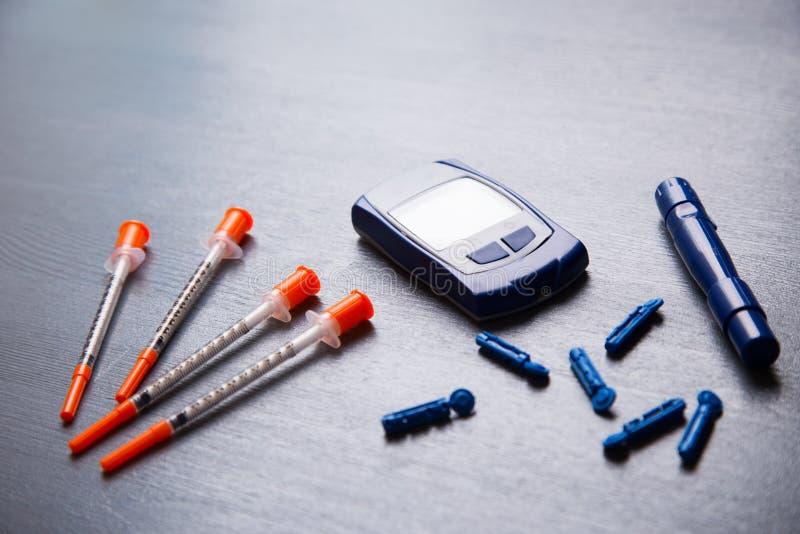Medidor da glicemia, agulhas e diversas seringas da insulina em uma tabela de madeira cinzenta, configuração lisa fotos de stock