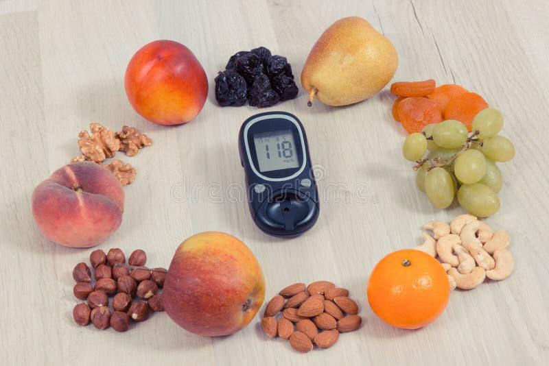 Medidor da glicose com resultado do nível do açúcar da medida e frutos saudáveis, conceito do diabetes e nutrição saudável imagem de stock