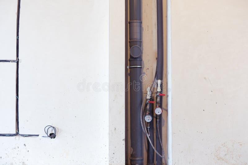 Medidor de água, tubulações da água de esgoto, fios A instalação do sistema do esgoto durante a renovação do apartamento fotografia de stock