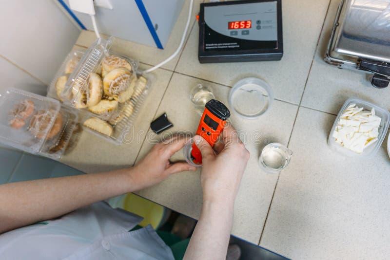 Medidor de pH del uso del científico en laboratorio en la fábrica de la comida para el producto del control y del análisis Produc fotografía de archivo