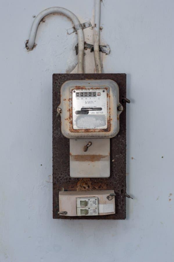 Medidor eletrônico doméstico indonésio da eletricidade nas paredes brancas fotos de stock