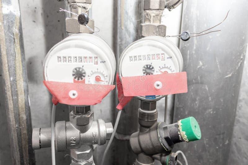 Medidores de água, contadores da água quente e fria na sala do serviço do banheiro em casa imagem de stock royalty free