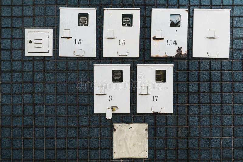 Medidores de fornecimento de eletricidade na parede telhada escura fotografia de stock
