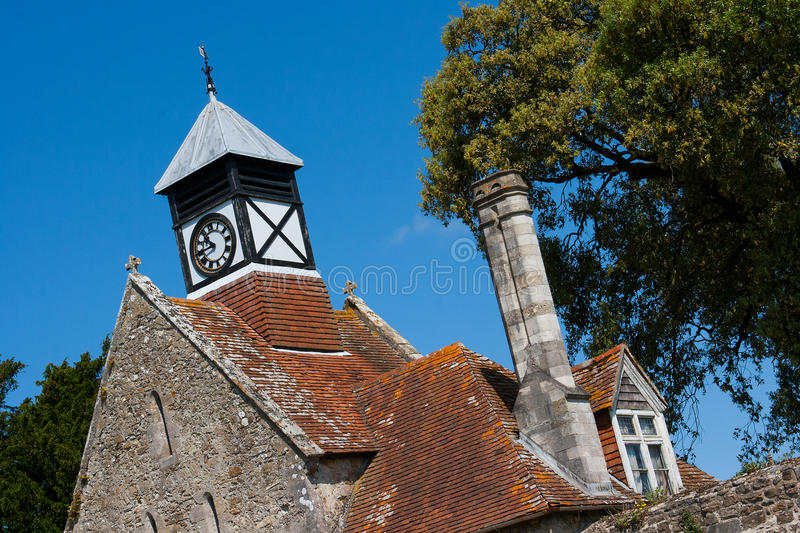 Medieval Abbey gate house and clock tower. Medieval Abbey gate house in Beaulieu in Hampshire England with Tudor clock tower and copper roof and tall chimneys. A royalty free stock photos