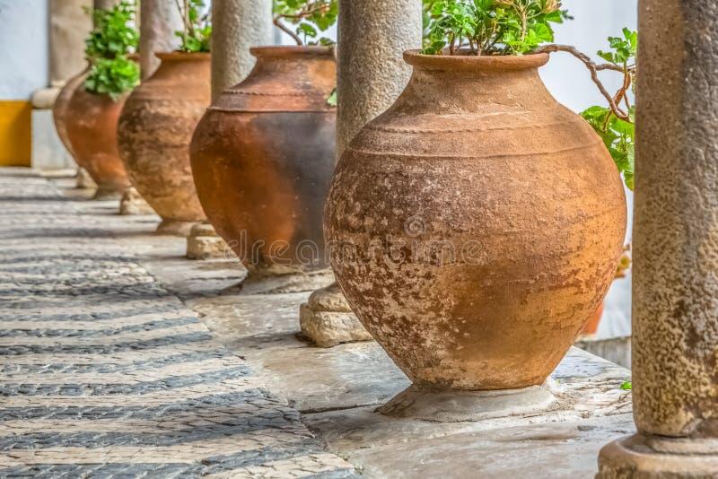 Medieval arcade view with orange ceramic vases and antique granite columns in Obidos stock image