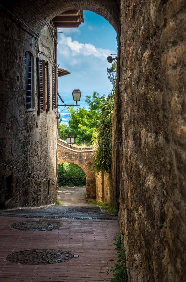 Medieval arched street in the old town of San Gimignano in Tuscany, Italy. View on the medieval arched street in the old town of San Gimignano in Tuscany, Italy royalty free stock images