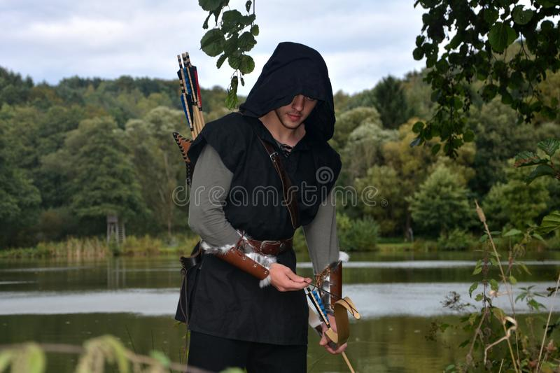 Medieval archer with black hood with the curve span before a lake and looks forwards. Medieval archer with black hood with the curve span before a little lake royalty free stock photography