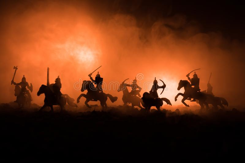 Medieval battle scene with cavalry and infantry. Silhouettes of figures as separate objects, fight between warriors on dark toned royalty free stock photos
