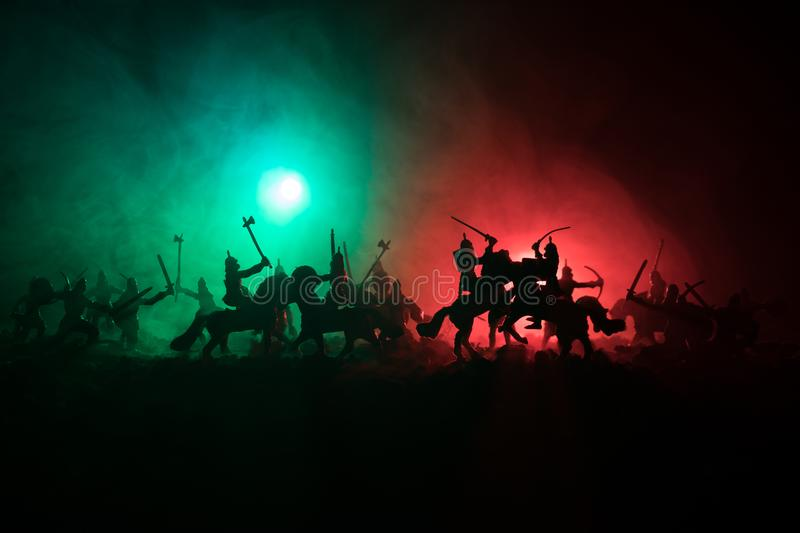 Medieval battle scene with cavalry and infantry. Silhouettes of figures as separate objects, fight between warriors on dark toned royalty free stock images