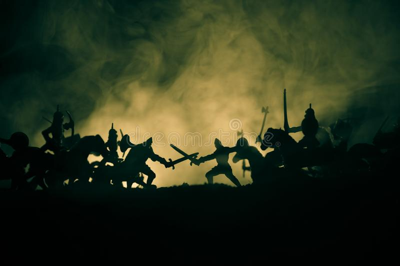 Medieval battle scene with cavalry and infantry. Silhouettes of figures as separate objects, fight between warriors on dark toned royalty free stock image