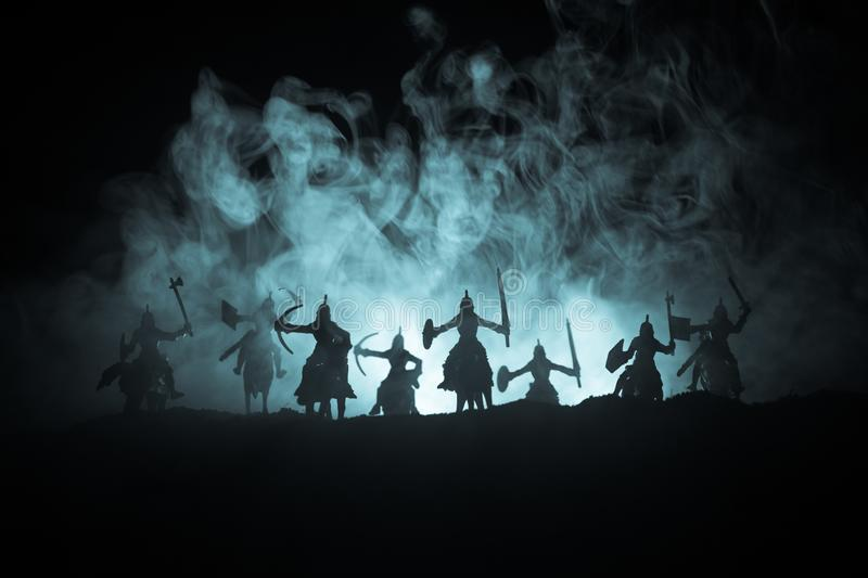 Medieval battle scene with cavalry and infantry. Silhouettes of figures as separate objects, fight between warriors on dark toned stock images