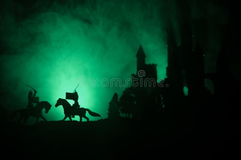Silhouettes of figures as separate objects, fight between warriors on dark toned foggy background with old gothic castle stock images