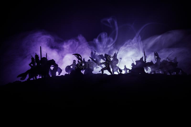 Medieval battle scene with cavalry and infantry. Silhouettes of figures as separate objects, fight between warriors on dark toned. Foggy background with royalty free stock photos