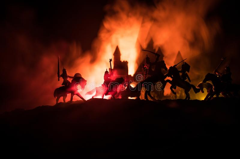 Medieval battle scene with cavalry and infantry. Silhouettes of figures as separate objects, fight between warriors on dark toned. Foggy background with royalty free stock image