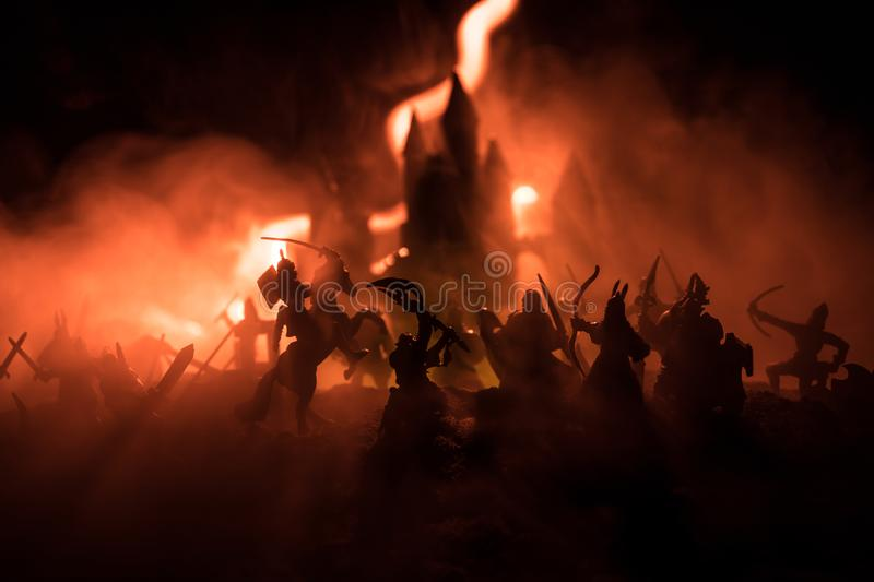 Medieval battle scene with cavalry and infantry. Silhouettes of figures as separate objects, fight between warriors on dark toned. Foggy background with stock photo