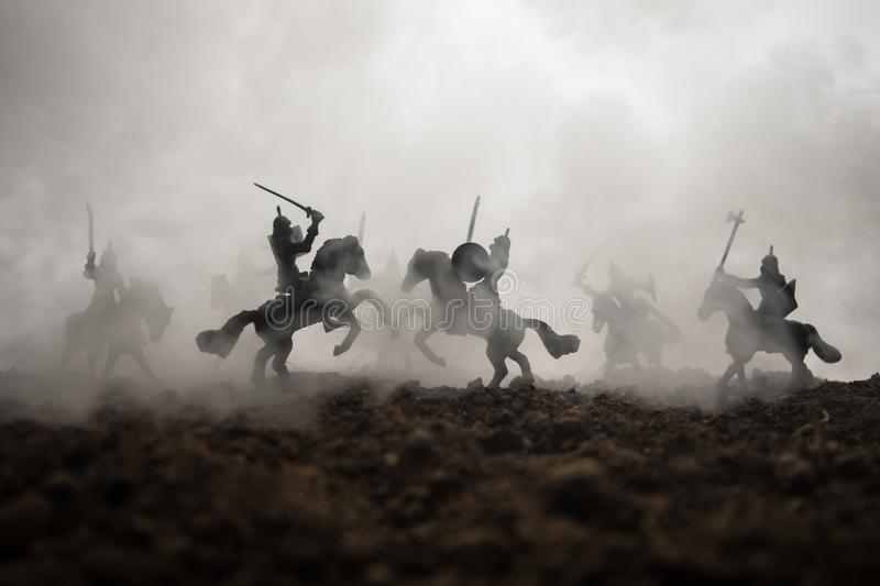 Medieval battle scene with cavalry and infantry. Silhouettes of figures as separate objects, fight between warriors on sunset royalty free stock photography