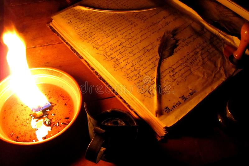 Medieval book with a feather pen and a candle in a medieval fair. stock photos