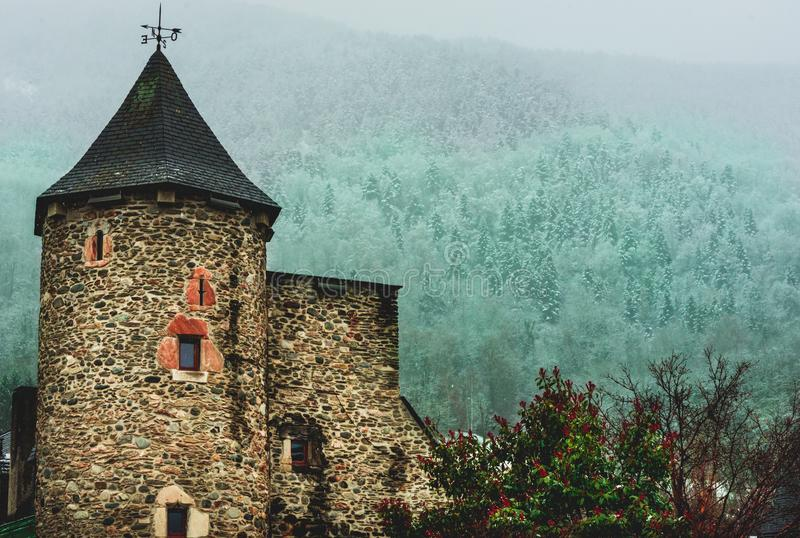 Medieval building and misty snowy forest in Saint-Lary, Pyrenees, France royalty free stock image