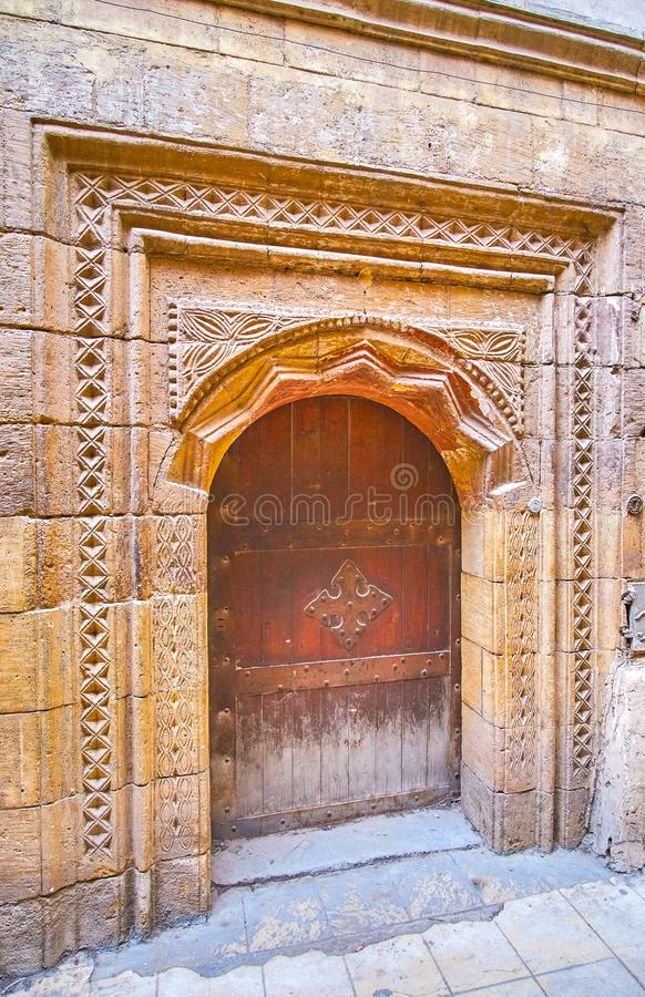 The medieval door in Coptic district of Cairo, Egypt. The medieval carved stone doorframe with metal cross on the door of the old edifice, in Coptic district of royalty free stock photo