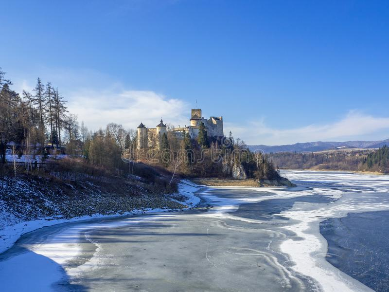 Medieval castle in Niedzica, Poland. In winter at partially frozen artificial Czorsztyn lake on Dunajec river royalty free stock photo
