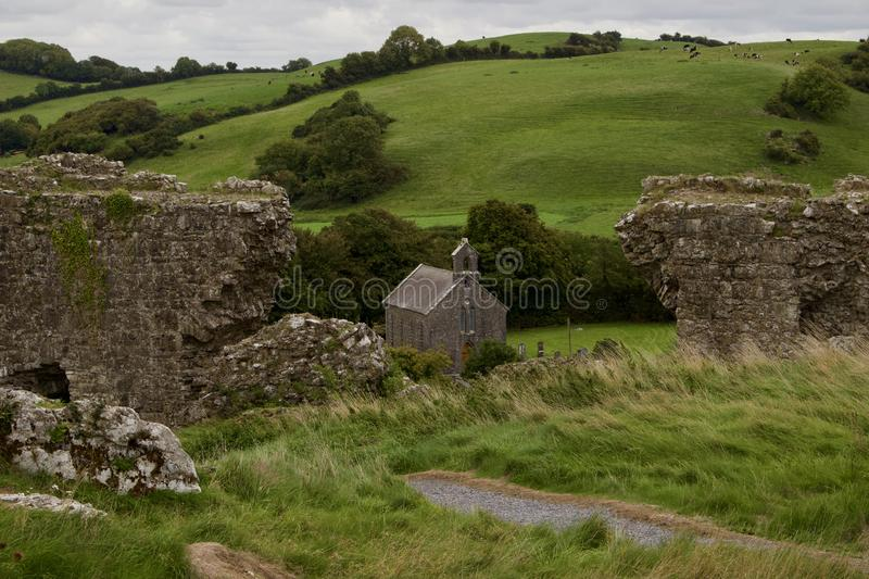 Medieval castle ruins in rural Ireland overlooking a modern church and Irish countryside stock photography
