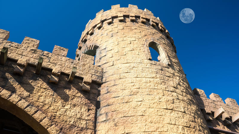 Medieval castle tower and walls. A medieval castle tower and walls made of bricks and with the blue sky with the full moon in the background royalty free stock image