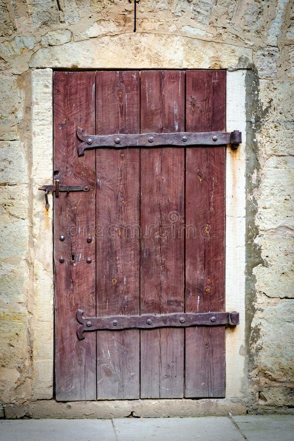 Medieval castle wooden door. With massive iron hinges stock photos