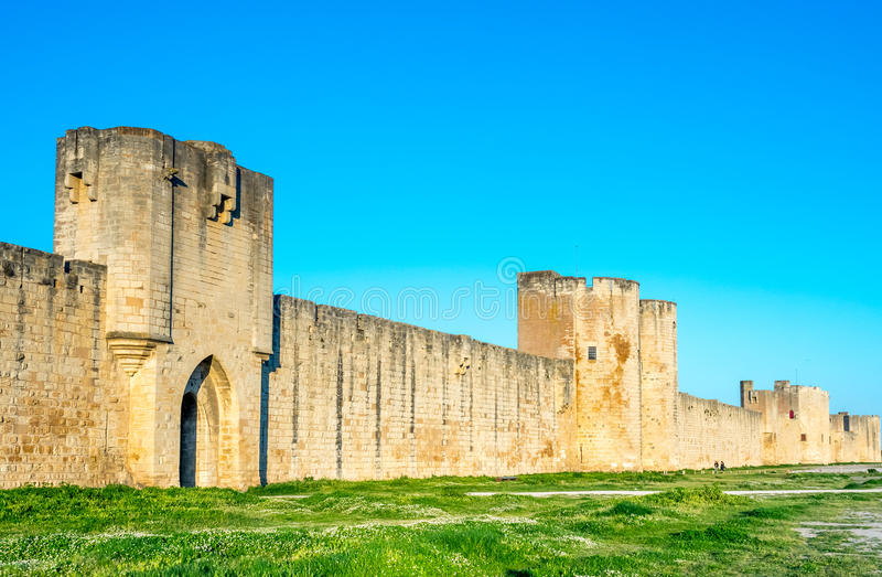 Medieval city wall of Aigues-Mortes city, France. Well preserved the Medieval city wall surrounding Aigues-Mortes city in France under blue sky royalty free stock image
