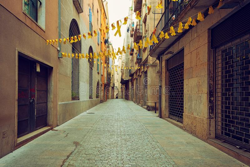 Girona, medieval cobblestone street view, downtown area. Medieval cobblestone street decorated with yellow ribbons - a symbol of independence - in the downtown stock image