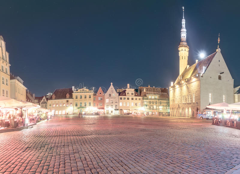 Medieval, dignified and festive town hall square of Tallinn after sunset. Retro styled image in pastel colors. Town hall building (Raekoda in Estonian) and Town stock images
