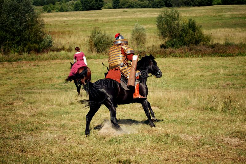 Medieval equestrian robber chases the horseback woman royalty free stock photos