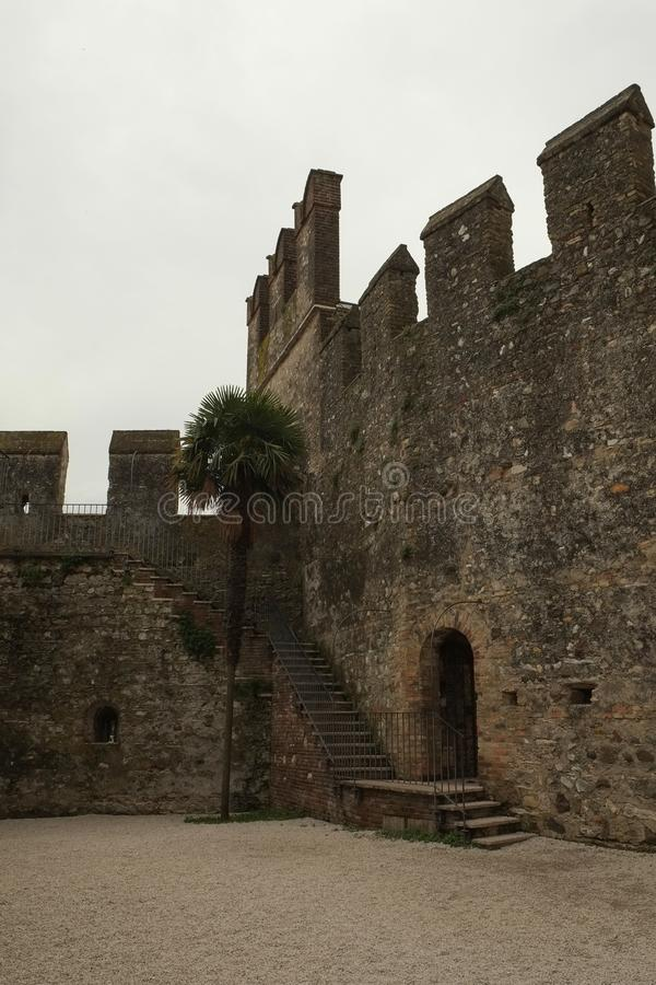Medieval fortress walls in Sirmione, Italy. Inner courtyard and Medieval fortress walls in Sirmione city, Italy royalty free stock photography