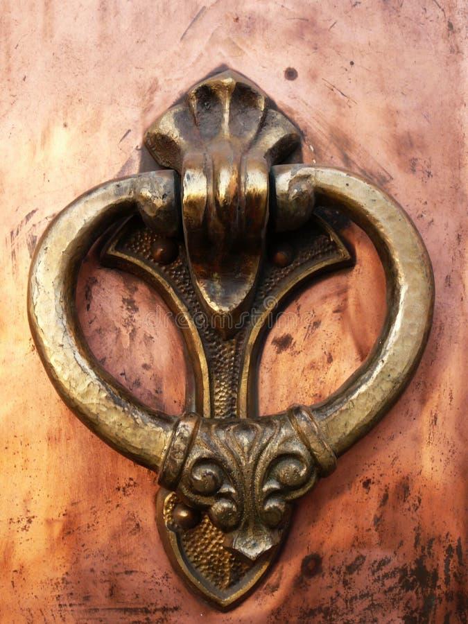 Medieval gate#2. Coppery wrought door knocker macro royalty free stock photos