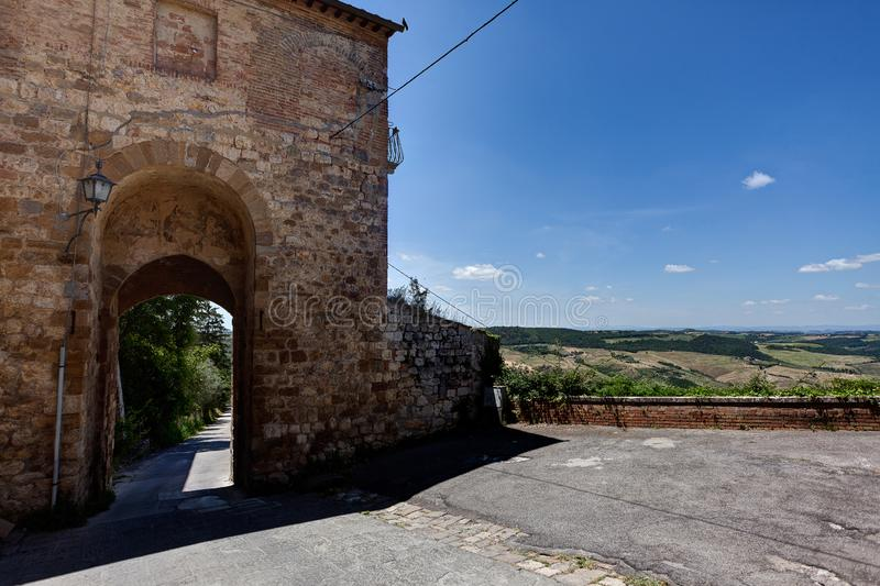 Medieval gate, Montepulciano, Tuscany, Italy. Surrounding defensive wall and gate, and landscape in the sun under the blue sky and strong shadow of Montepulciano royalty free stock images