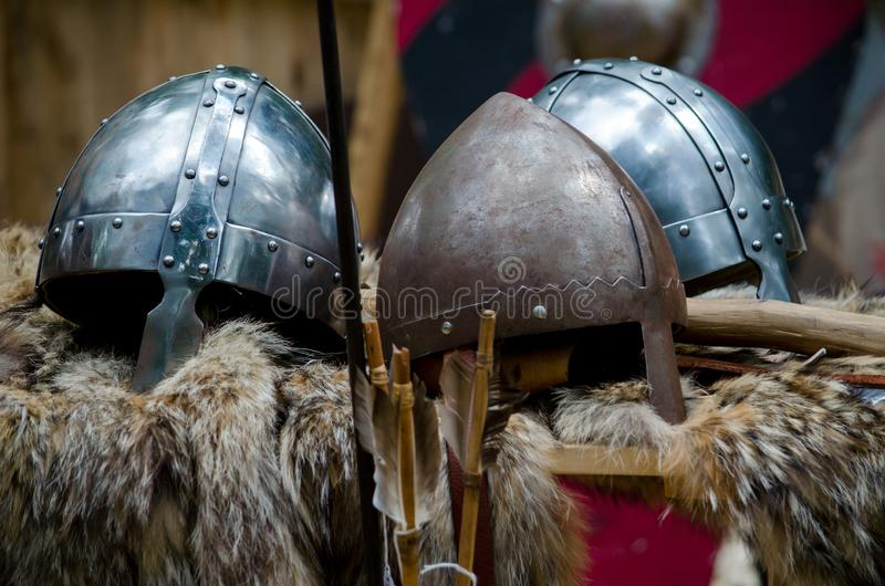 Medieval helmets on display at a Renascence fair. Reproduction medieval helmets and accessories resting on fur pelts, are on display at a renascence fair in the stock photos