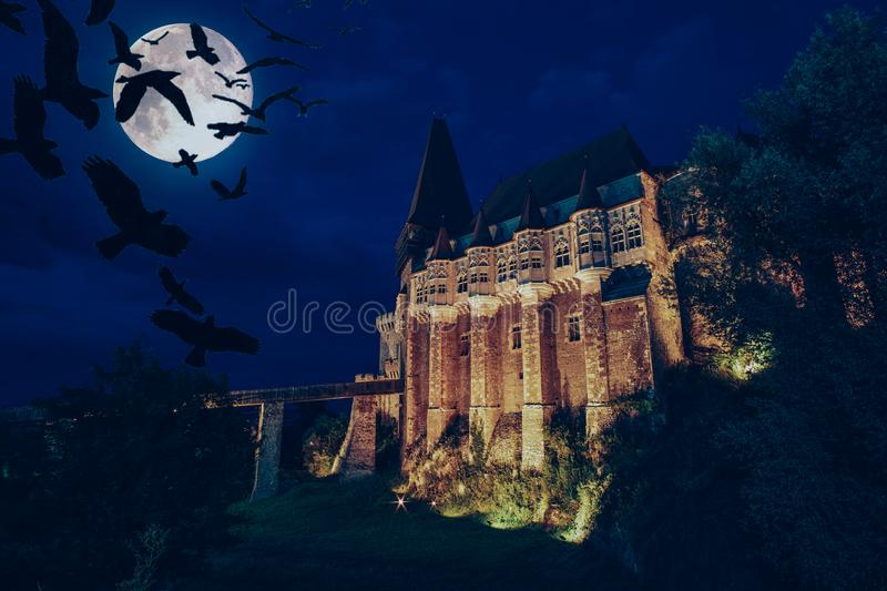 medieval Hunedoara castle in Transylvania, full moon, crows at night - Halloween background stock photography