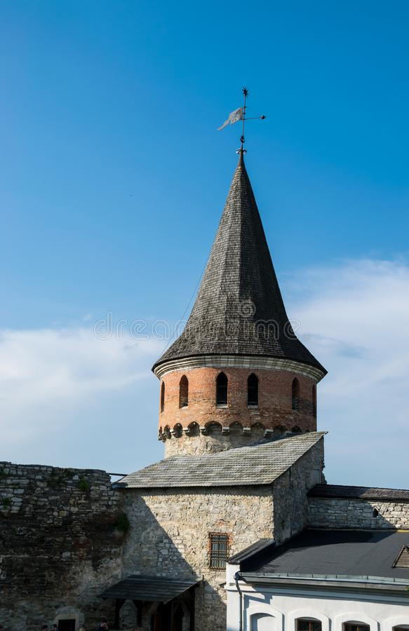 Medieval castle tower. Medieval Kamianets-Podilskyi Castle in Ukraine. Fortress of early 14th century. Tower and fortification walls. Spire on blue sky royalty free stock image