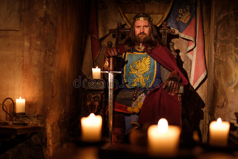 Medieval king on throne in ancient castle interior. stock photos