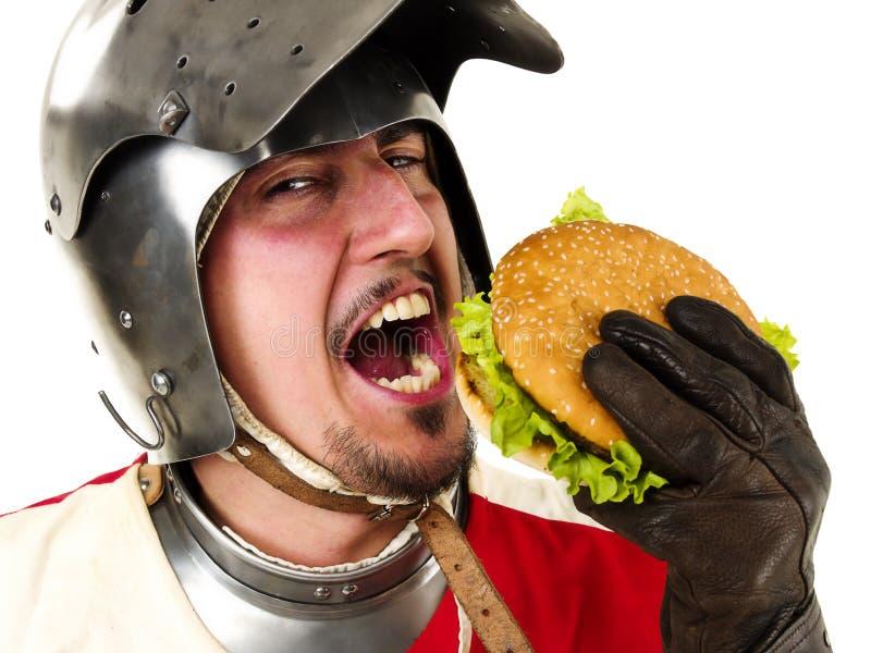 Medieval knight eating a hamburger. Medieval knight eating a tasty hamburger royalty free stock photos