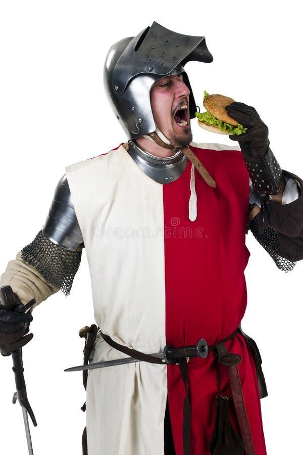 Medieval knight eating a tasty hamburger. Medieval knight eating a hamburger royalty free stock images