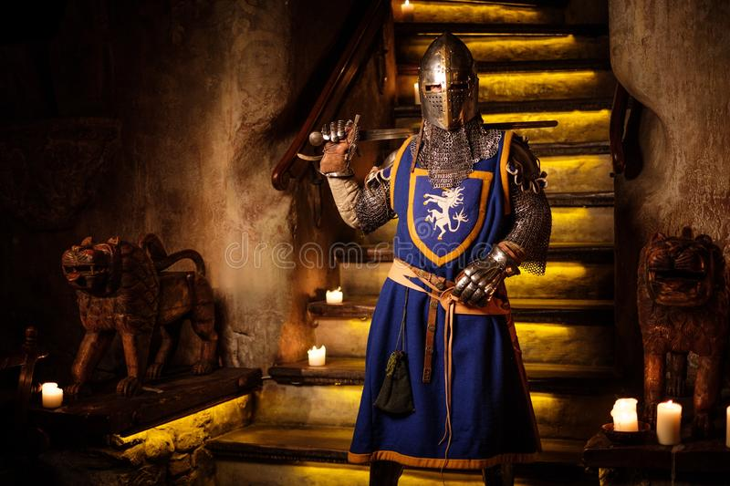 Medieval knight on guard in ancient castle interior. stock image