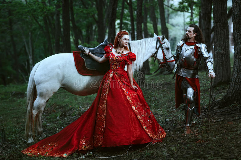 Medieval knight with lady. Medieval knight with his beloved lady in red dress royalty free stock photo