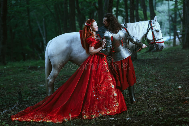 Medieval knight with lady. Medieval knight with his beloved lady in red dress royalty free stock photos