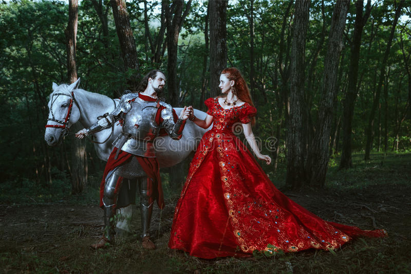 Medieval knight with lady. Medieval knight with his beloved lady in red dress stock image