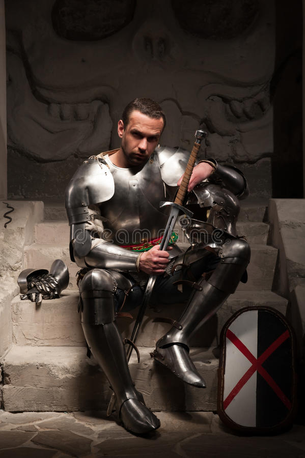 Medieval knight sitting on the steps of ancient royalty free stock photography