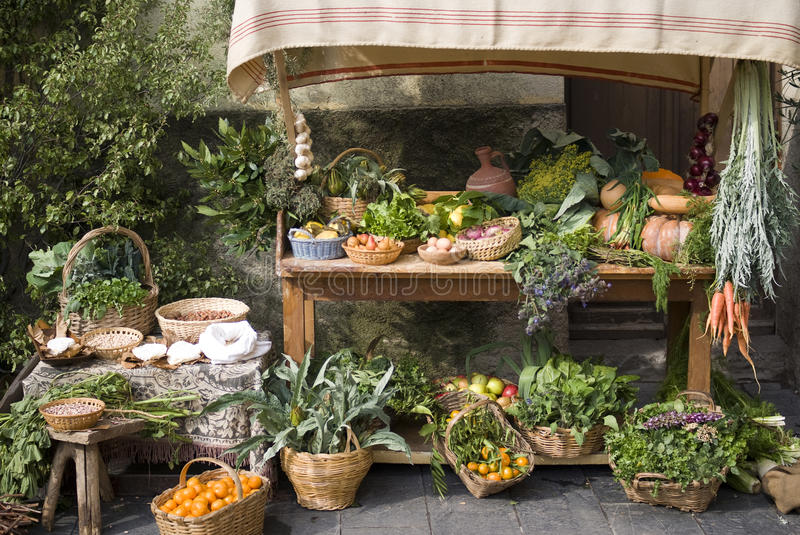 Medieval market stall selling fruit. Fruit and vegetable stall at a medieval market stock image