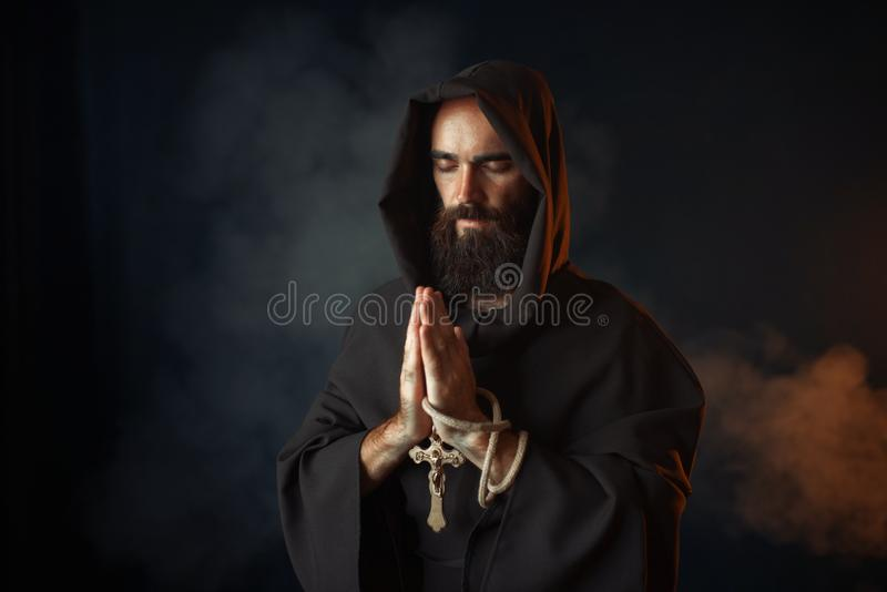 Medieval monk praying with closed eyes. Medieval monk in black robe with hood praying with closed eyes, secret ritual. Mysterious friar in dark cape. Mystery and stock photography